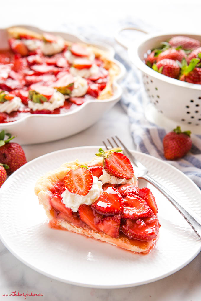 slice of fresh strawberry pie on white plate with fork