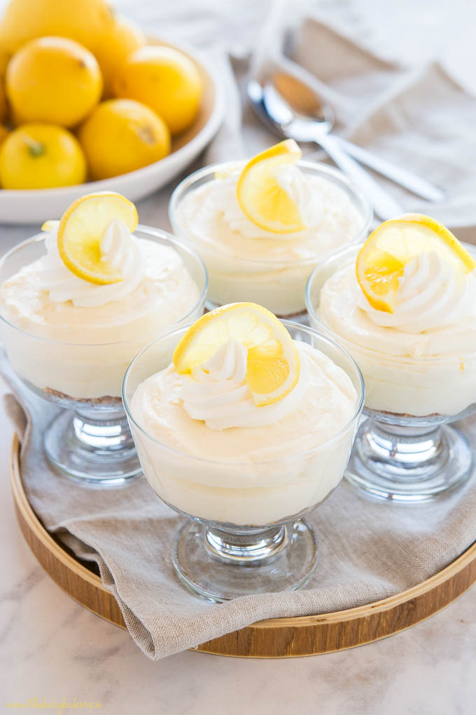 no bake lemon cheesecakes in glass dishes with whipped cream and lemon slices