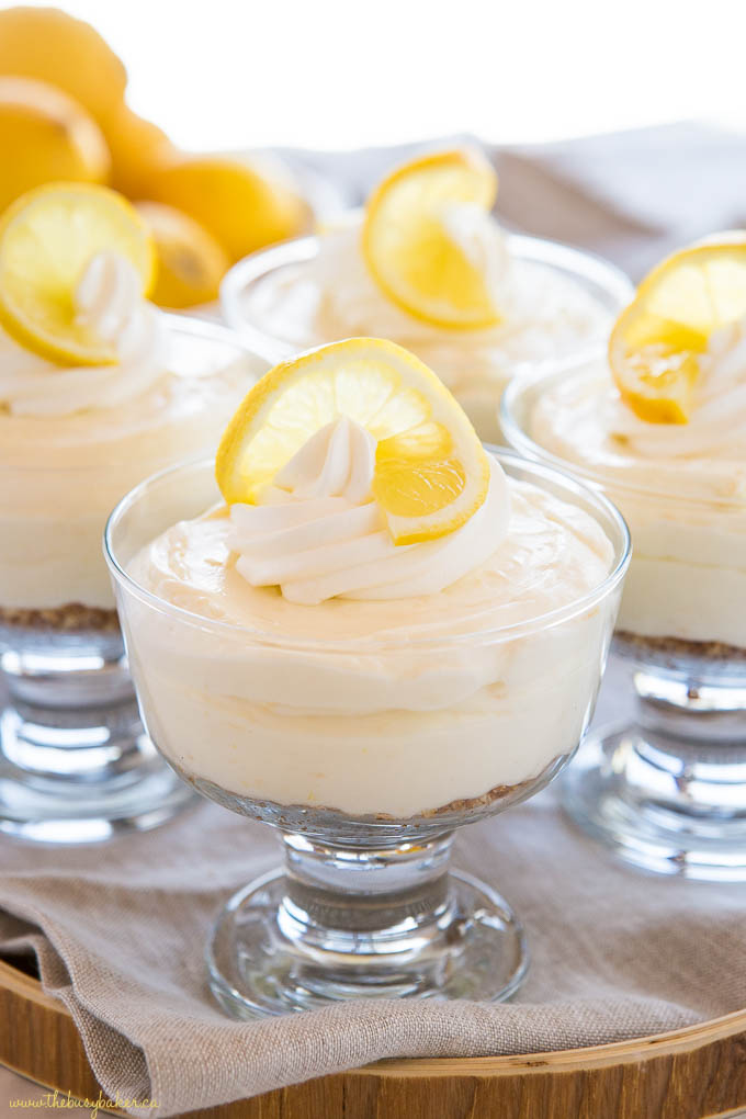 mini no bake lemon cheesecakes in glass dishes with whipped cream and lemon slices