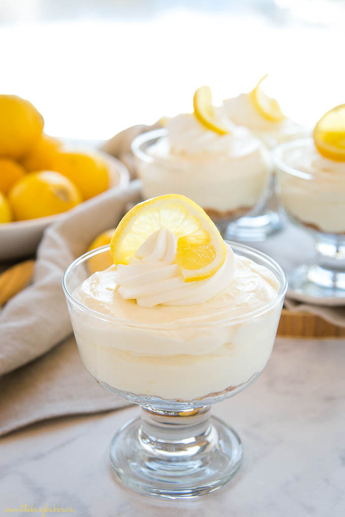 no bake lemon cheesecake with whipped cream and lemon slice, in a stemmed glass dish