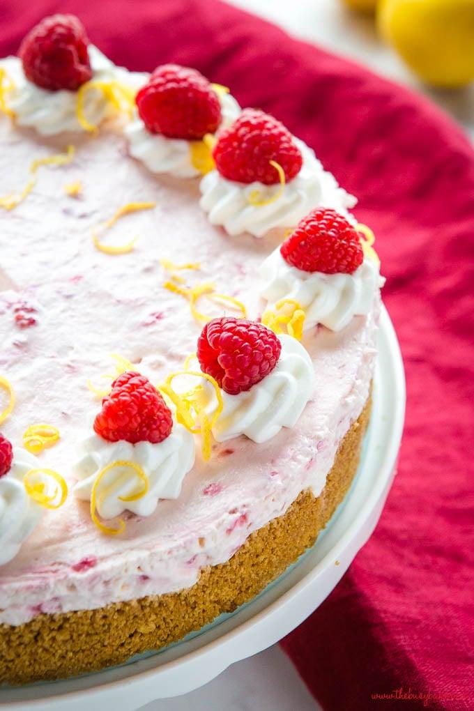 no bake lemon raspberry cheesecake with whipped cream, lemon zest and raspberries