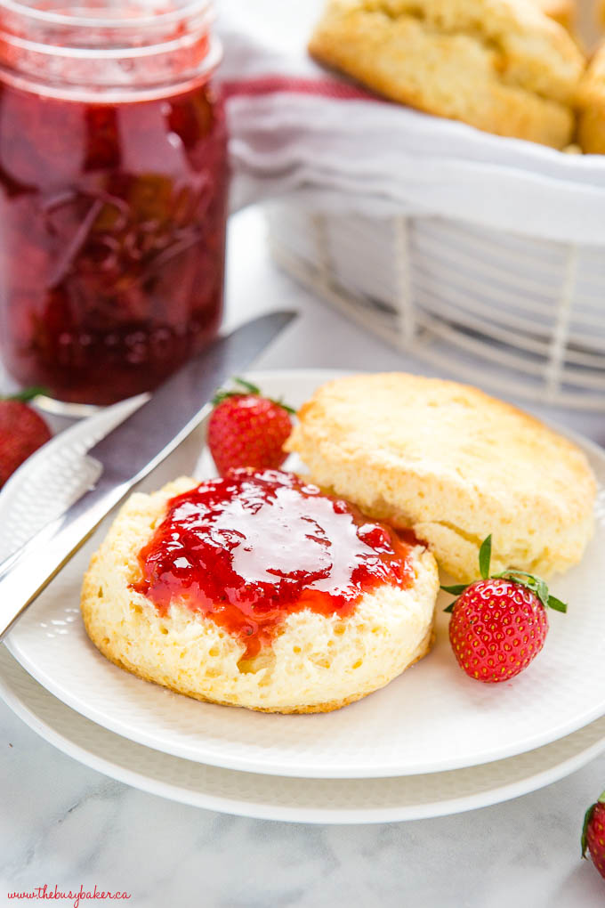 scone on white plate with strawberry jam