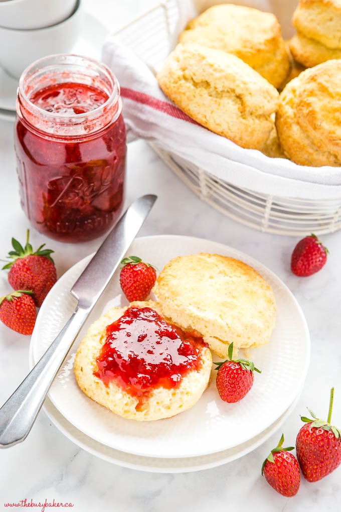 scone on white plate with strawberry jam, fresh strawberries, and a knife