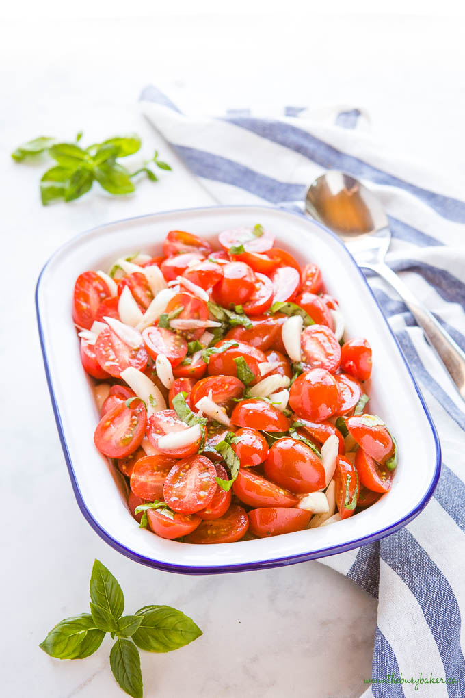 tomato onion salad with fresh basil in white enamel dish