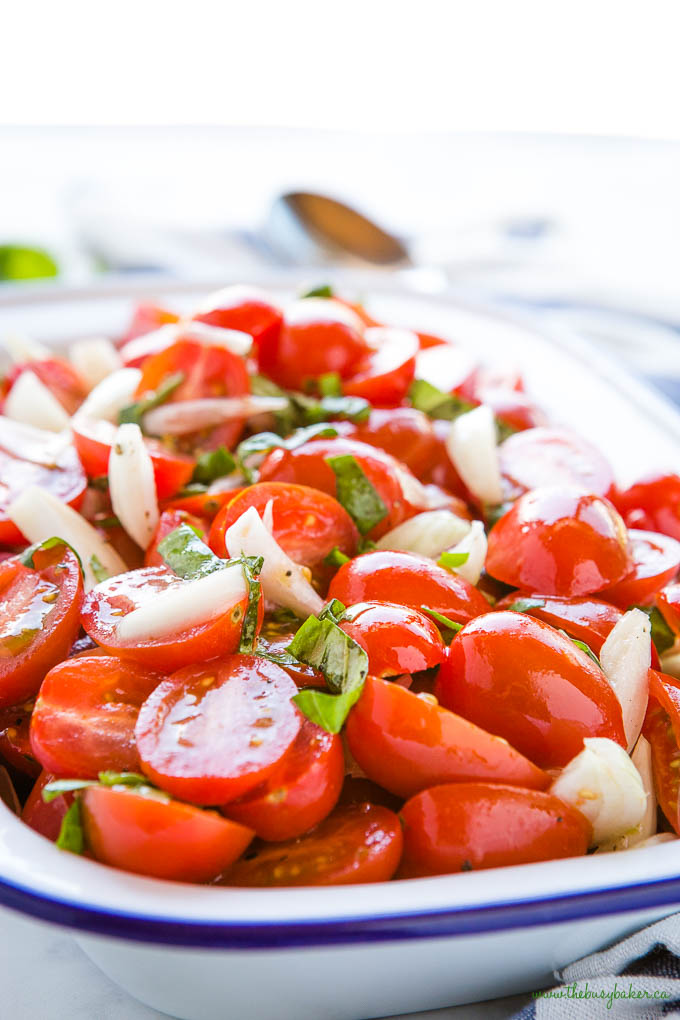 tomato onion salad with fresh basil in white and blue enamel bowl