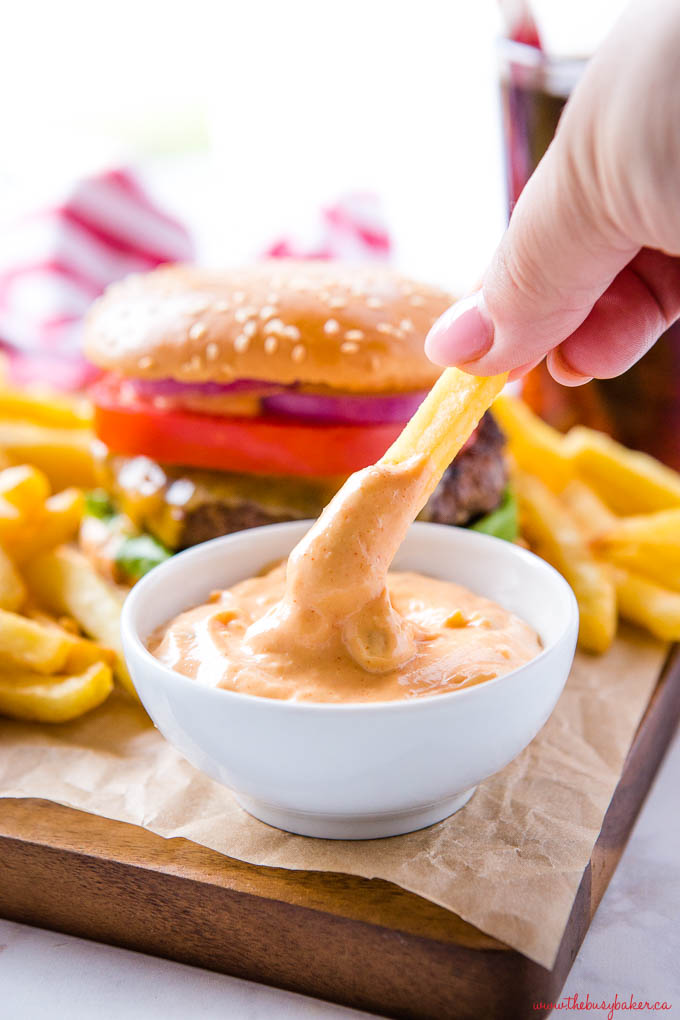 woman's hand dipping french fry into a small white dish containing burger sauce