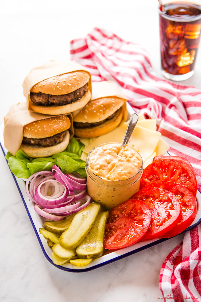 platter of 3 burgers with fixings and a jar of burger sauce with a spoon