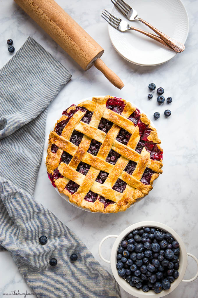 overhead image: blueberry pie with colander of blueberries, rolling pin, dessert plates with copper forks, and striped kitchen towel