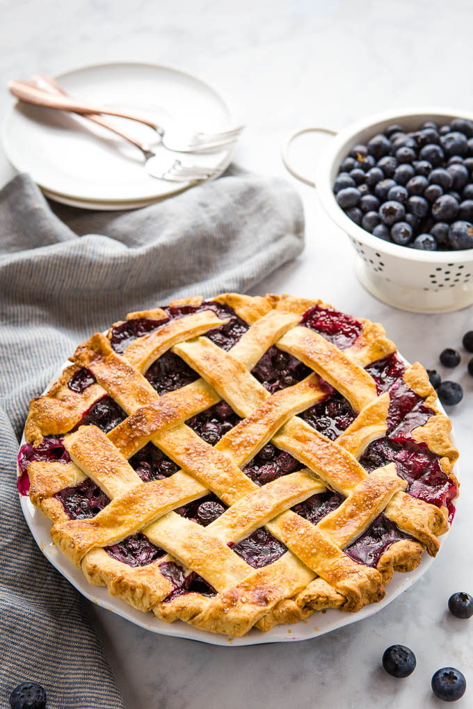 blueberry pie with fresh blueberries, dessert plates with forks and striped kitchen towel