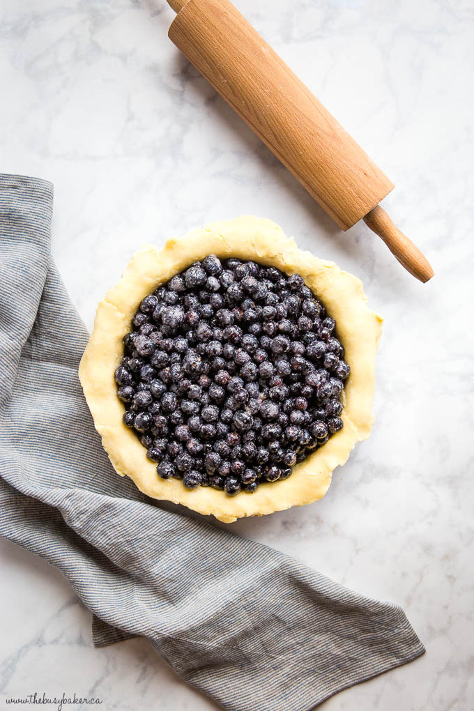overhead image: raw pie crust filled with fresh blueberries, a rolling pin, and a striped kitchen towel