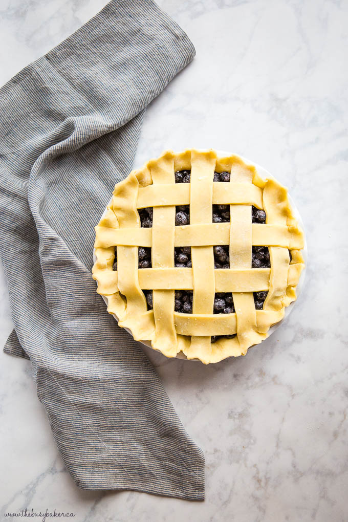 overhead image: unbaked blueberry pie with lattice crust, on a marble backdrop