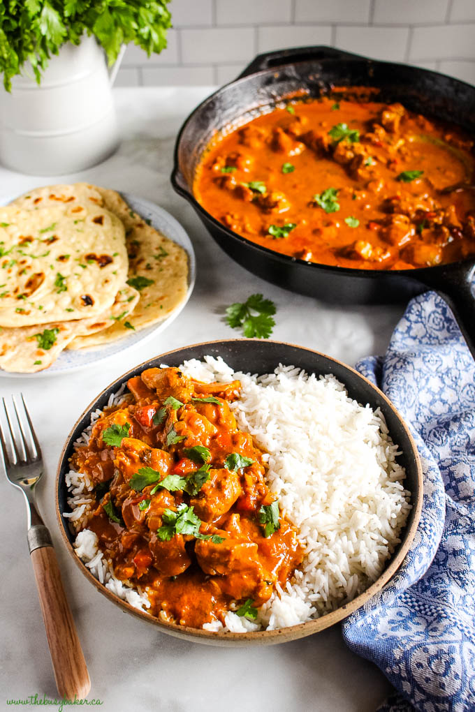 butter chicken with rice and cilantro in a bowl