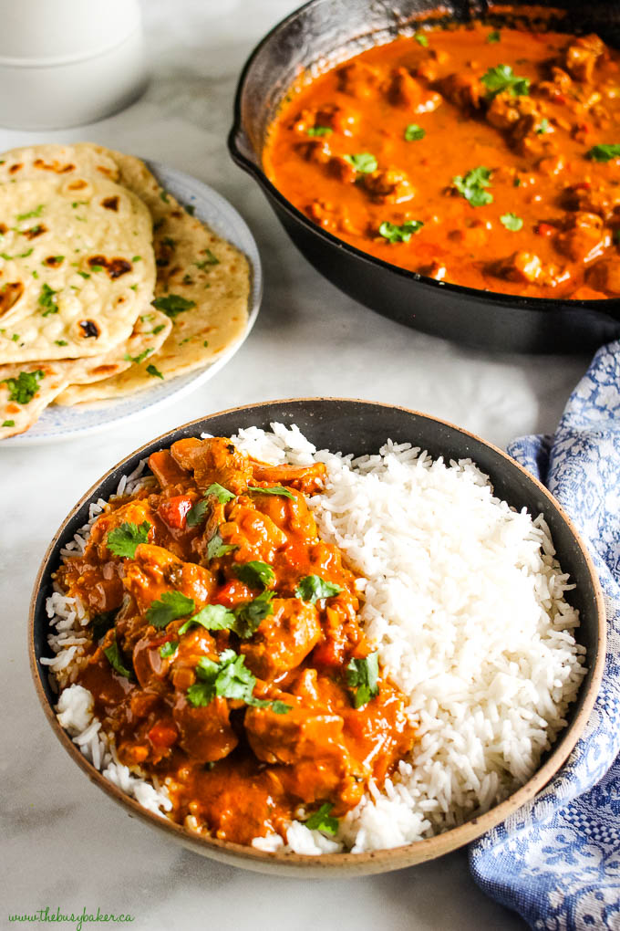 butter chicken with rice in black bowl with naan bread