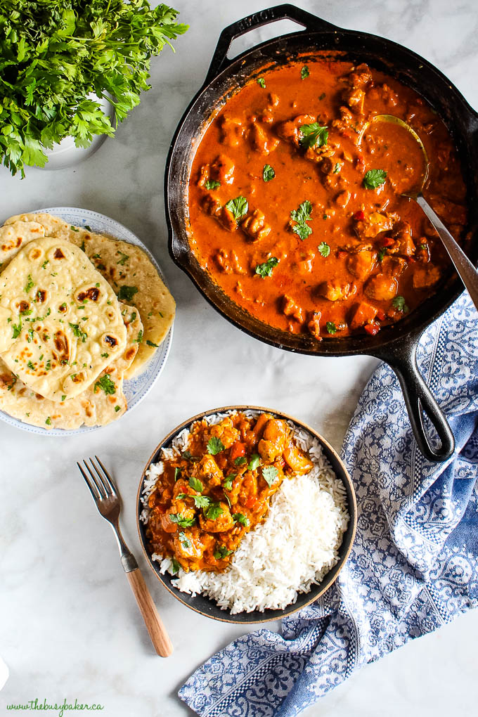 overhead image: cast iron skillet with butter chicken, a plate with naan bread, and butter chicken over rice in a black bowl