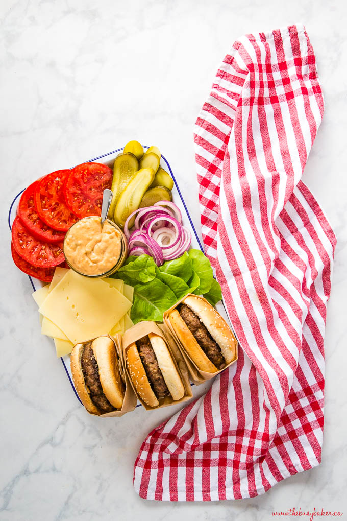 overhead image: platter of homemade burgers with sesame seed buns, lettuce, cheese, tomatoes, pickles, onions and burger sauce