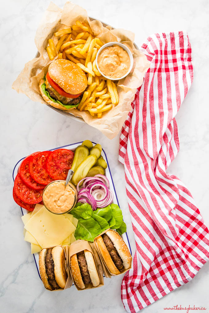 overhead image: cheeseburger platter with french fries, and 3 hamburgers with fixings on platter