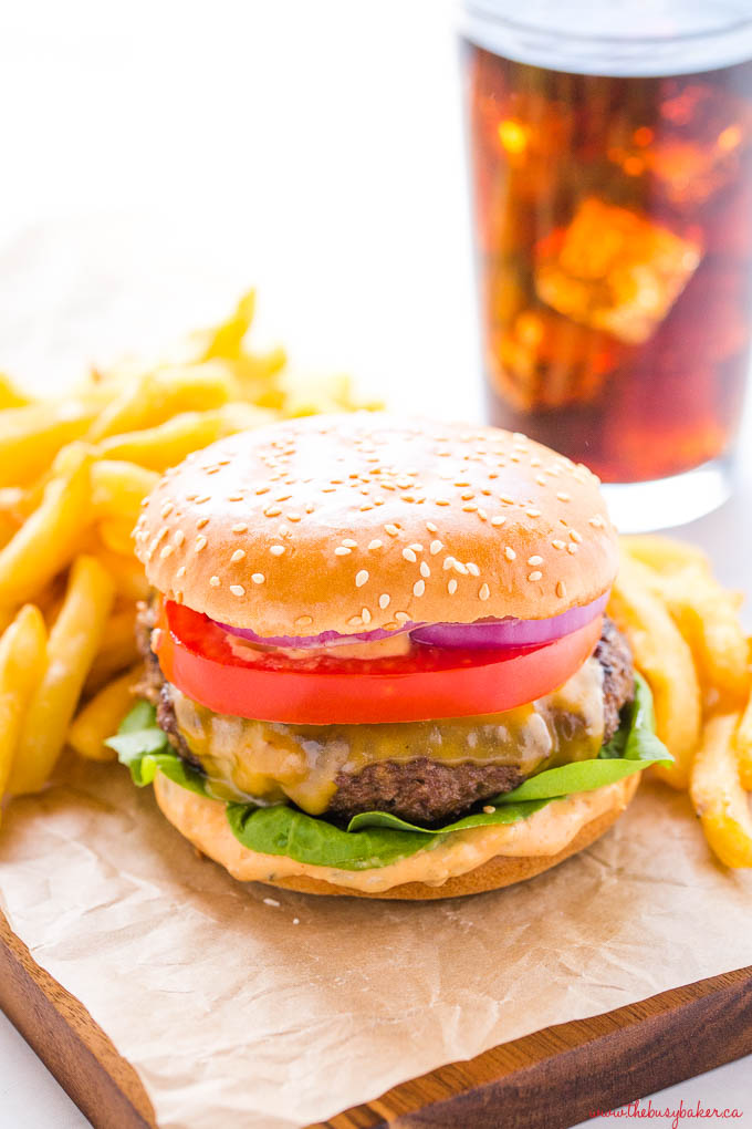 homemade cheeseburger on sesame seed bun with fries and coke with ice