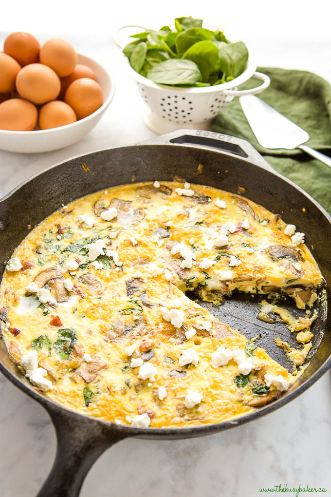 cast iron skillet with spinach mushroom egg frittata with a slice missing