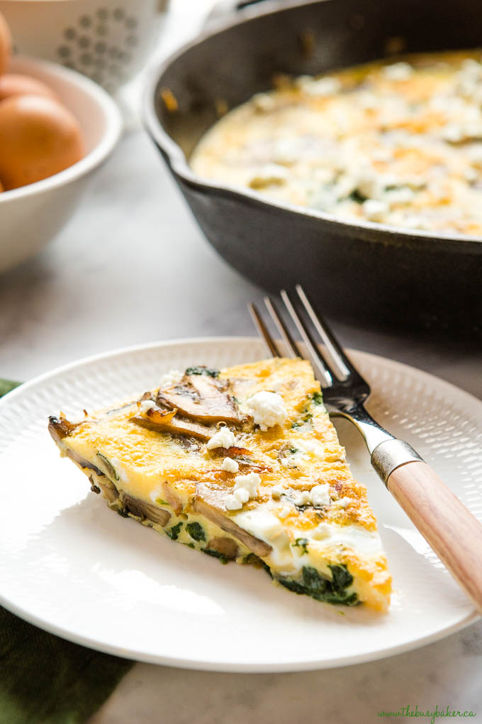 slice of mushroom spinach frittata on white plate with wooden handled fork