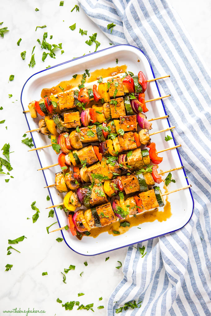 overhead image: tofu veggie skewers for the grill on white tray with blue rim and fresh herbs