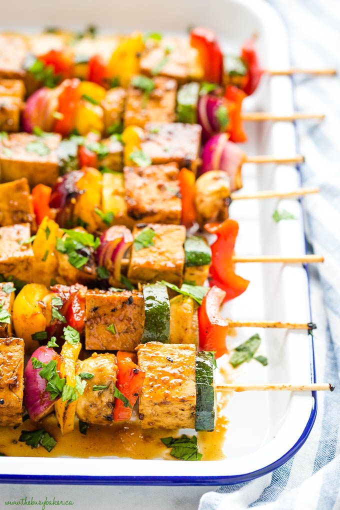 marinated tofu veggie skewers in white tray with blue rim