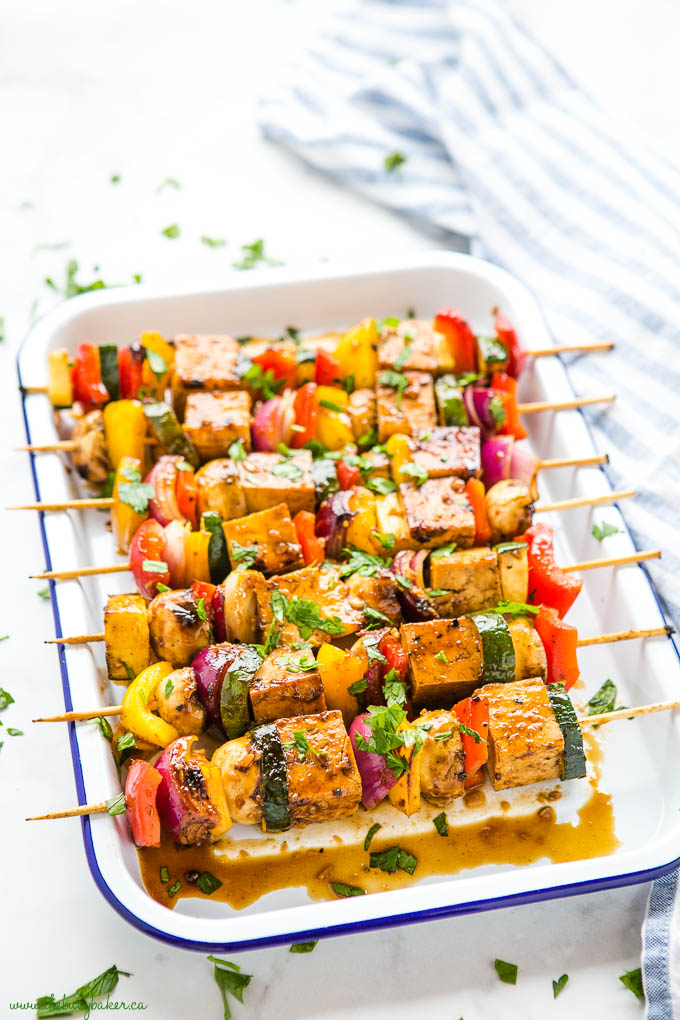 marinated tofu veggie skewers in white enamel baking tray