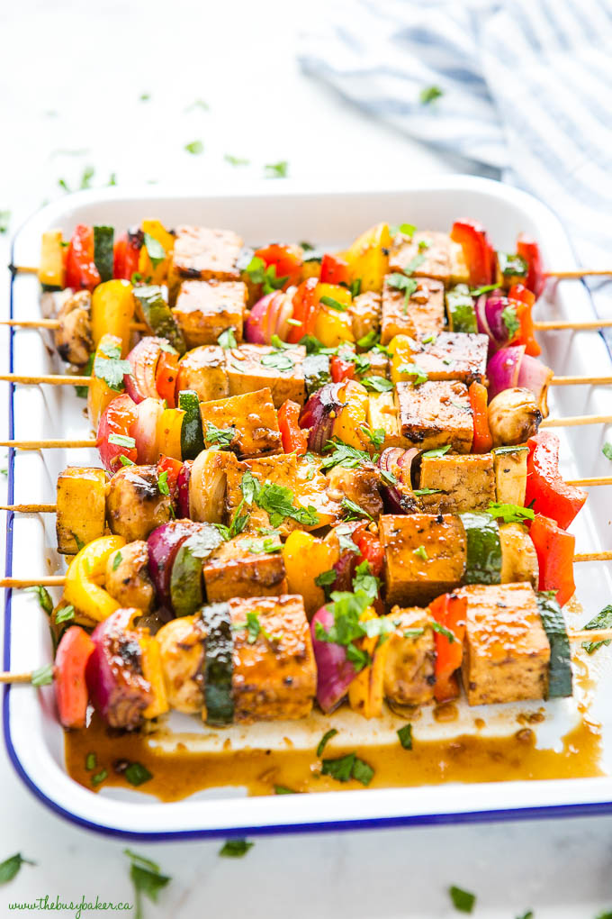 tofu veggie skewers in white serving tray with blue rim