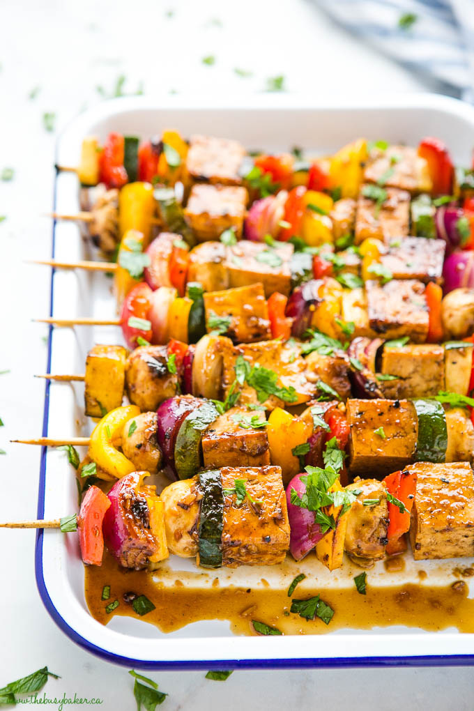 veggie skewers with tofu and fresh herbs in white enamel baking tray with blue rim