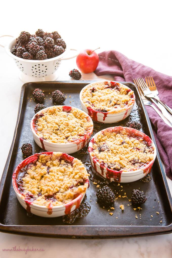 single serving apple blackberry crumble on a dark baking sheet with fresh blackberries