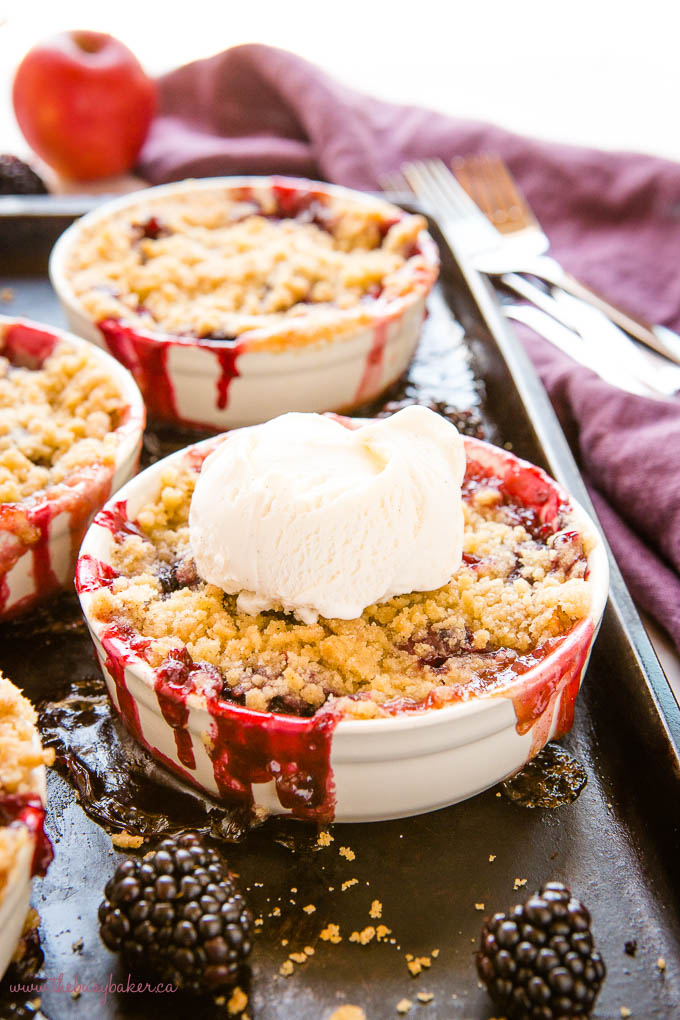single serving of apple blackberry crumble in a white ramekin with a scoop of vanilla ice cream