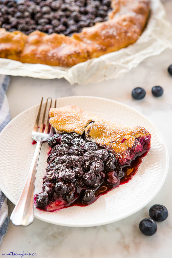 slice of blueberry galette on white plate with fork