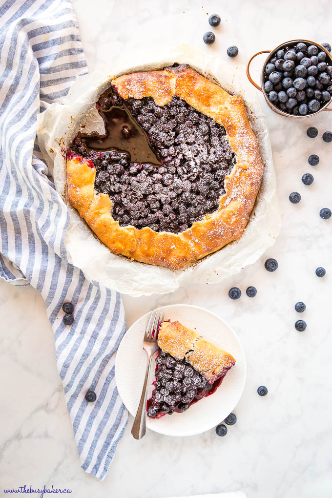 overhead image: blueberry galette with a slice missing, slice of blueberry galette on white plate with a fork
