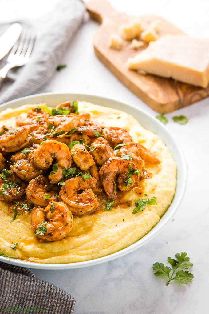 cajun shrimp over creamy cheesy polenta with fresh herbs in blue bowl