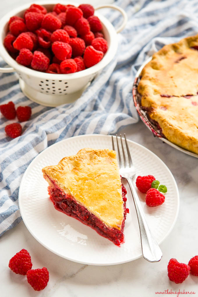 slice of raspberry pie on white plate with fork and fresh raspberries