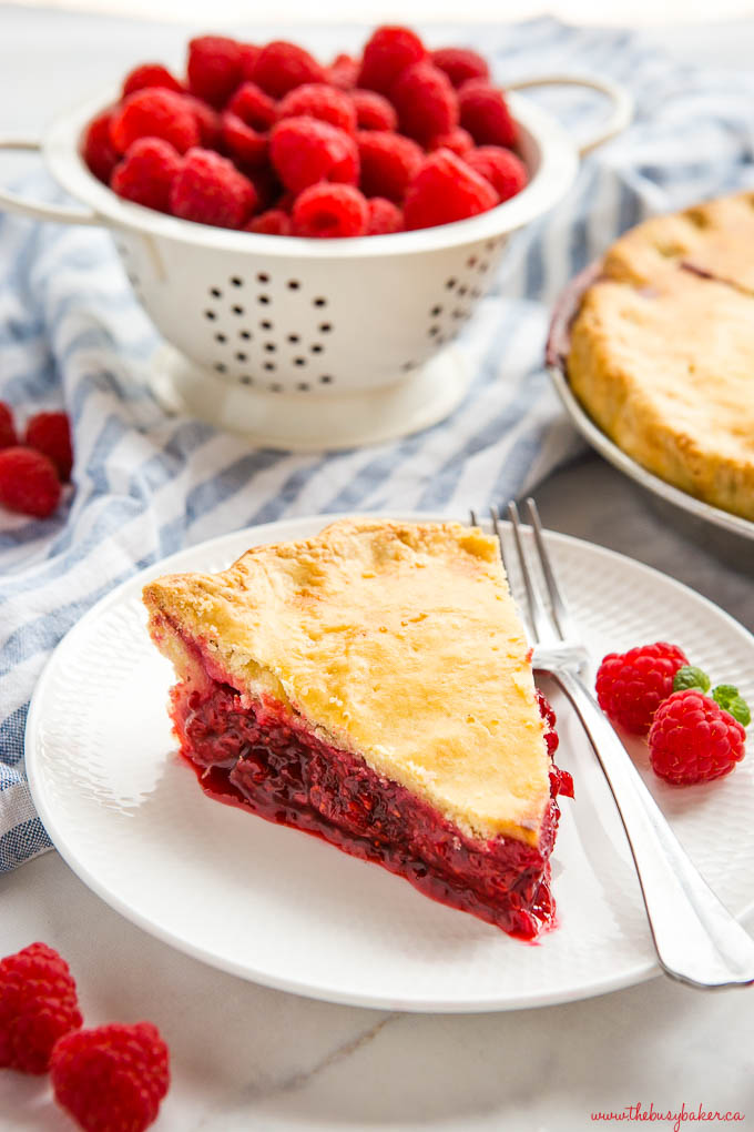 slice of raspberry pie on white plate with fork