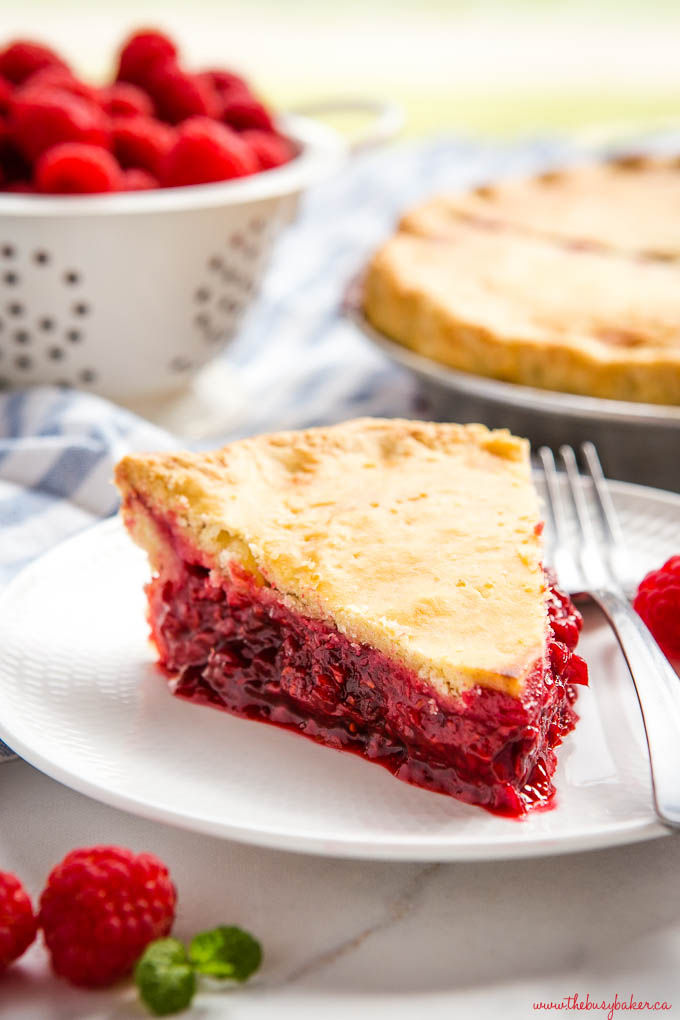 slice of fresh raspberry pie with juicy raspberry filling on white plate with fork