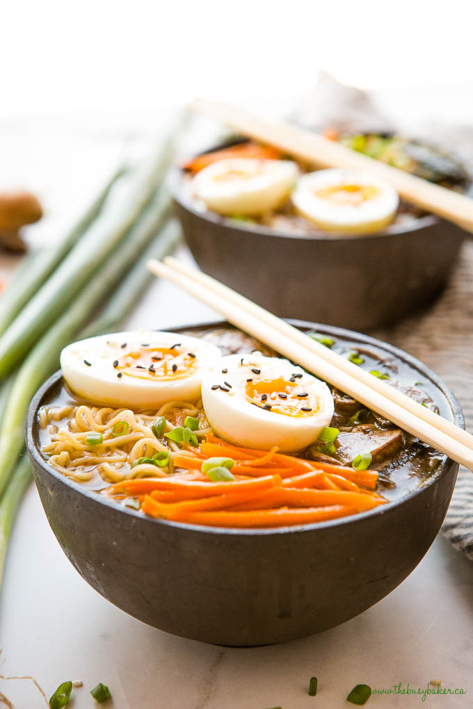 easy ramen bowl in black bowl with carrots, noodles, eggs, green onions, and sesame seeds