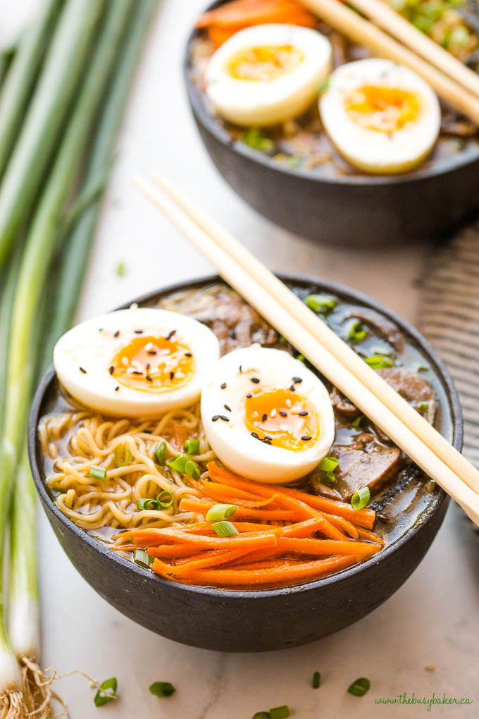 closeup image: vegetarian ramen with eggs, carrots, noodles, green onions, and chopsticks