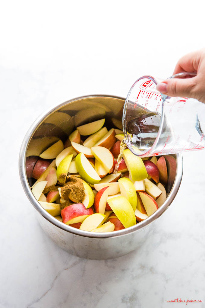 hand pouring water into instant pot with apples and cinnamon