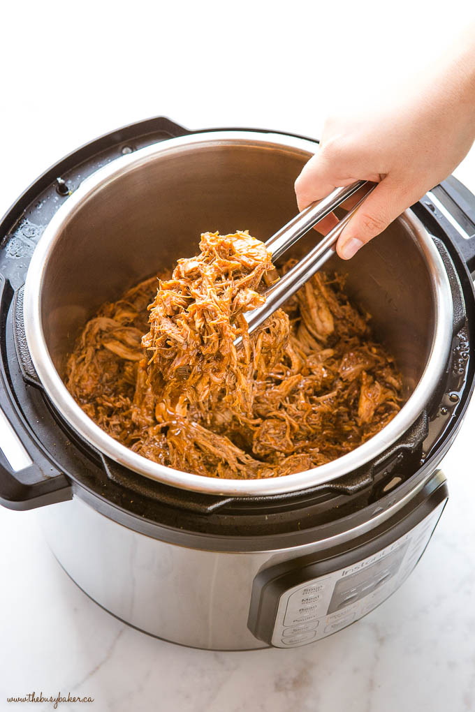 Hand gripping tongs, holding pulled pork from the Instant Pot