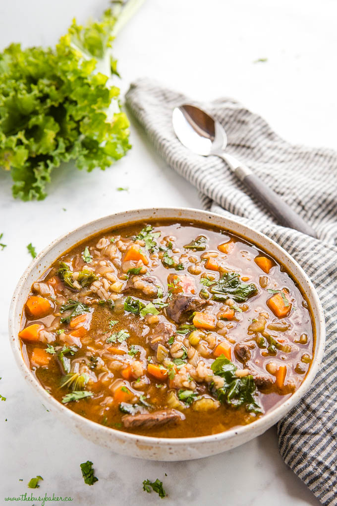 beef soup with carrots, kale and barley in ceramic bowl