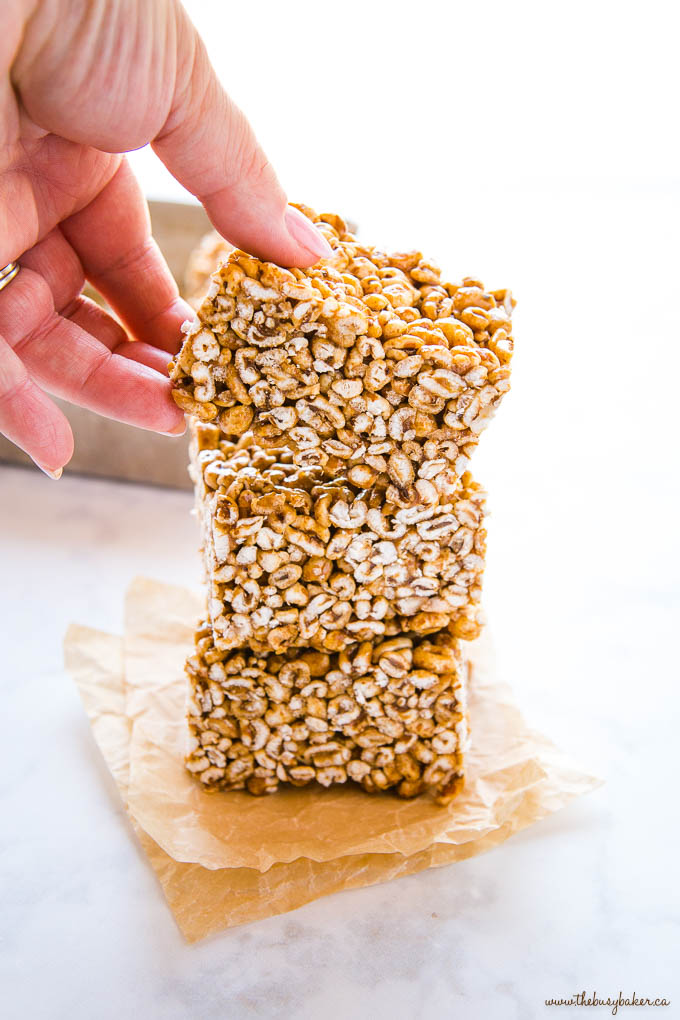 hand reaching for a piece of puffed wheat cake