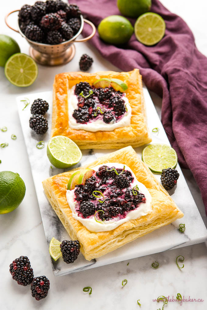 blackberry lime tarts on a marble board with fresh blackberries and lime zest