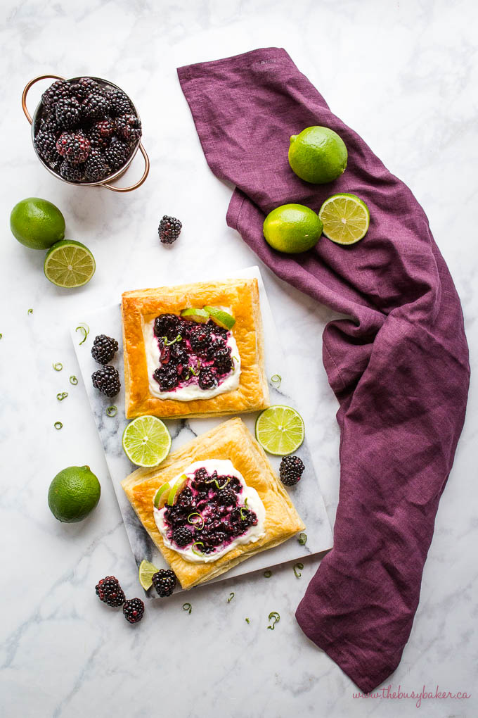 overhead image: puff pastry danishes with creamy filling, lime, and fresh blackberries on a marble background with a purple kitchen towel