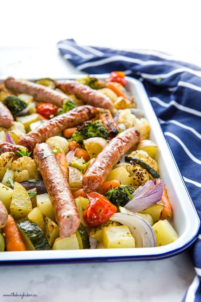 chicken sausage sheet pan dinner on whit enamel baking sheet