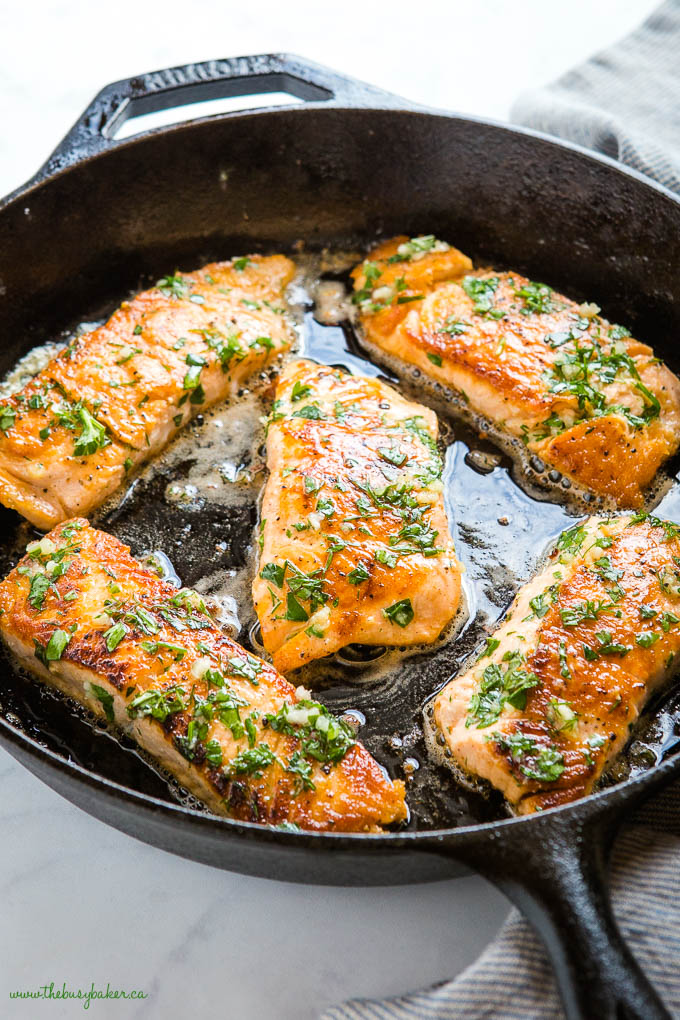 cast iron pan with salmon filets, with herb and garlic butter sauce