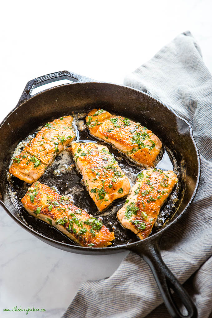 herb and garlic butter salmon filets in cast iron pan