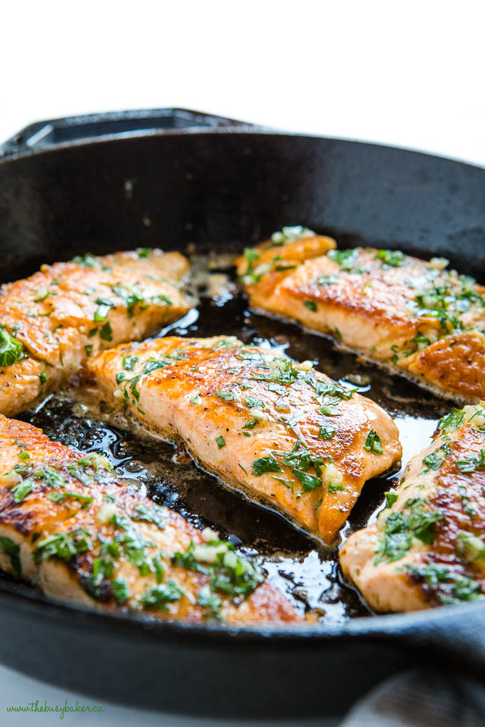 cast iron pan with salmon filets with herbs