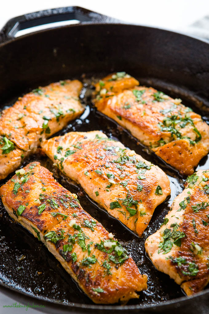 salmon filets with herb garlic butter sauce in cast iron pan
