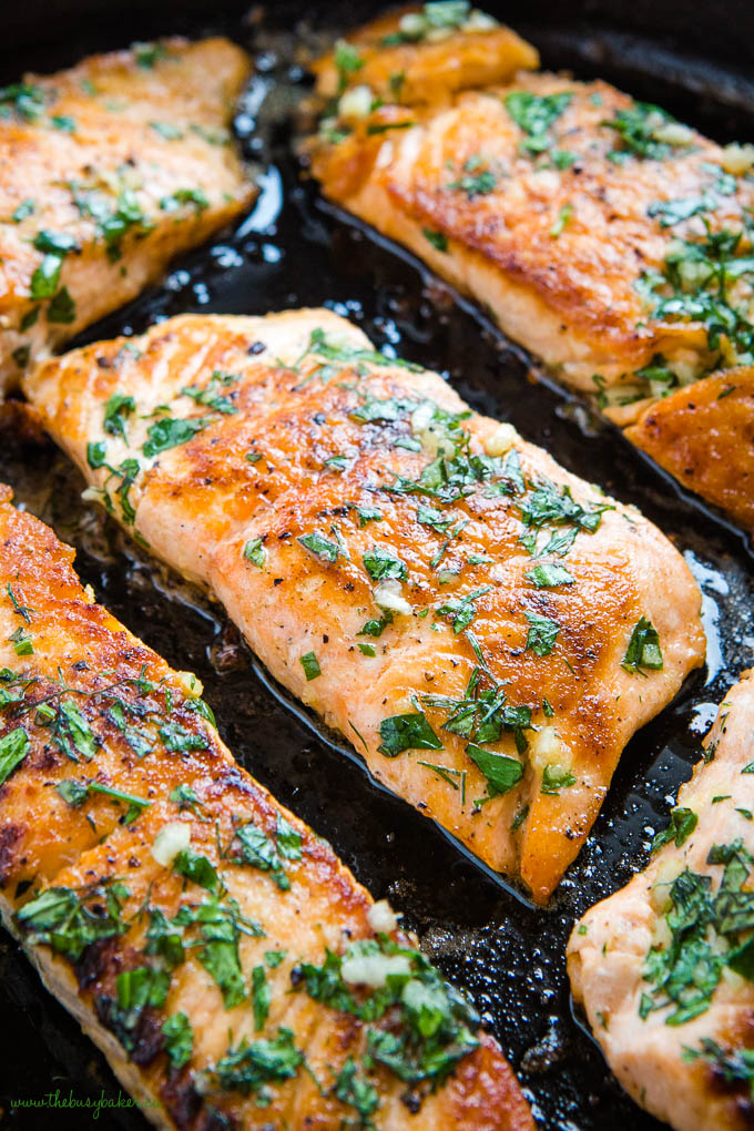 closeup image of salmon filet with garlic herb butter sauce